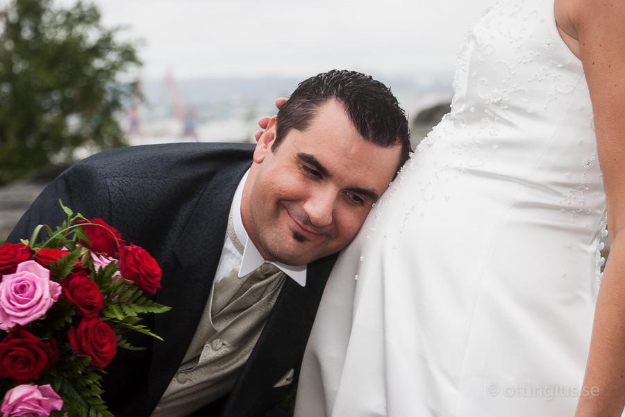 Brudgummen med sin gravida brud, skickar en hälsning till sitt ofödda barn