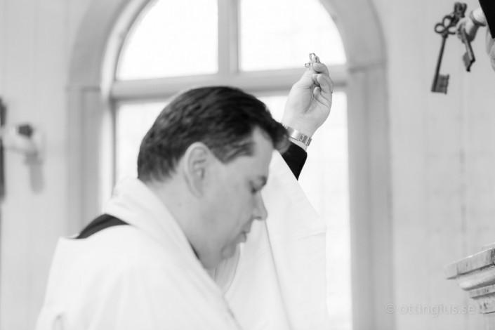 Prästen välsignar ringarna under vigselakten