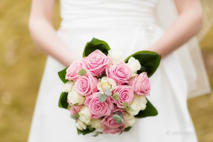 Brudbukett i rosa och gult fotograferad mot den vita bröllopsklänningen