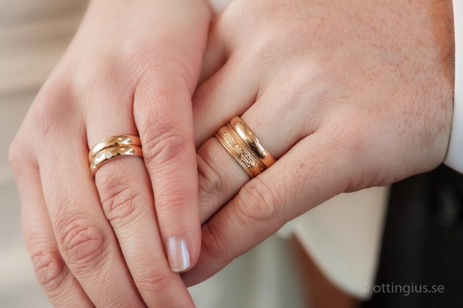 Bröllopsfoto på brudparets händer, med vigselringarna på