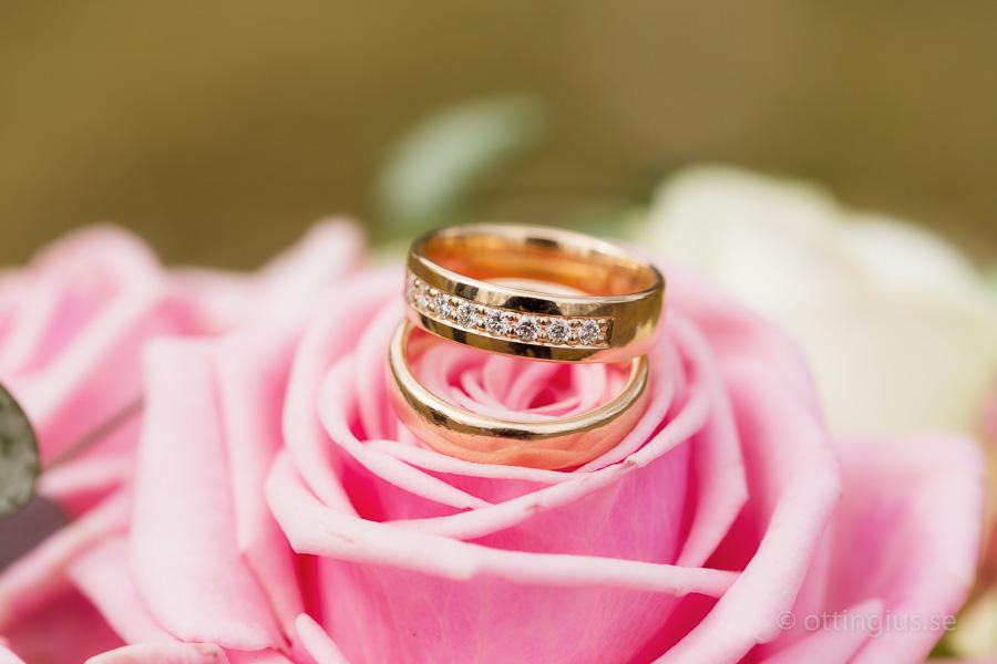 Vigselring i guld mot den rosa brudbuketten