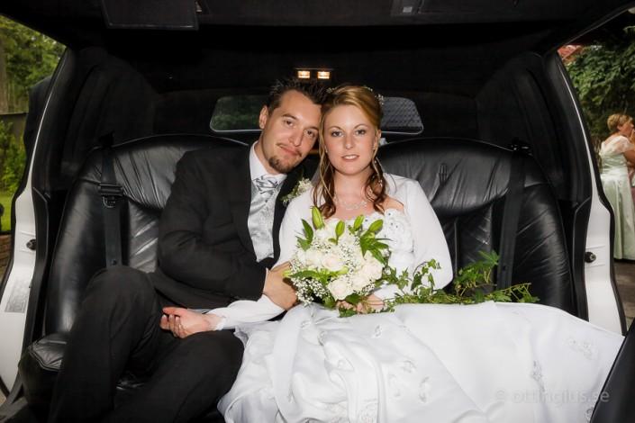 Brudparet poserar för bröllopsfoto i limousinen